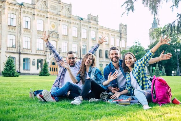 バックパックや他のものと幸せな美しい学生チームが話し、楽しんで、屋外の大学の芝生でリラックスしています