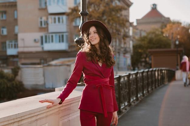街の通りを歩く紫色のスーツの幸せな美しいスタイリッシュな女性、帽子をかぶって、財布を持って春夏秋シーズンのファッショントレンド