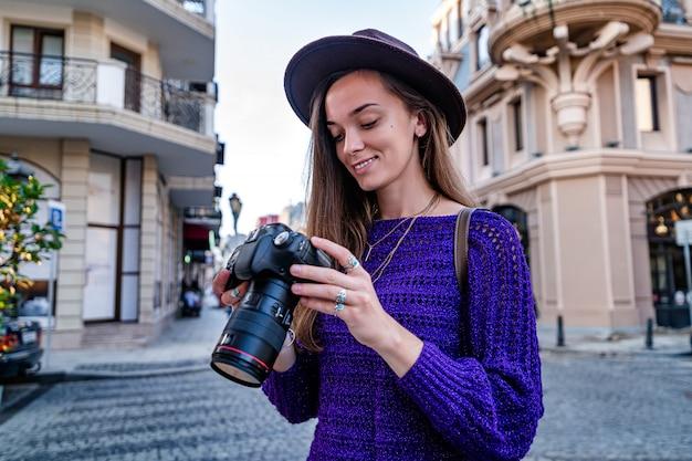 Счастливый красивый стильный фотограф женщины в шляпе смотря фото на камере dslr после фотографировать пока гуляющ вокруг европейского города