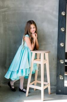 Счастливая красивая удивленная милая прекрасная очаровательная маленькая девочка с зубастой улыбкой, она носит голубое платье, положила руки на табуретку, изолированную на ярко-сером фоне, copyspace