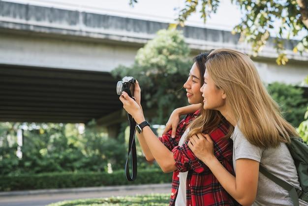 幸せな美しい旅行者アジアの友人の女性はバックパックを運ぶ
