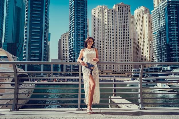 ドバイで楽しんでいるファッショナブルな夏の白いドレスで幸せな美しい認識できない観光客の女性