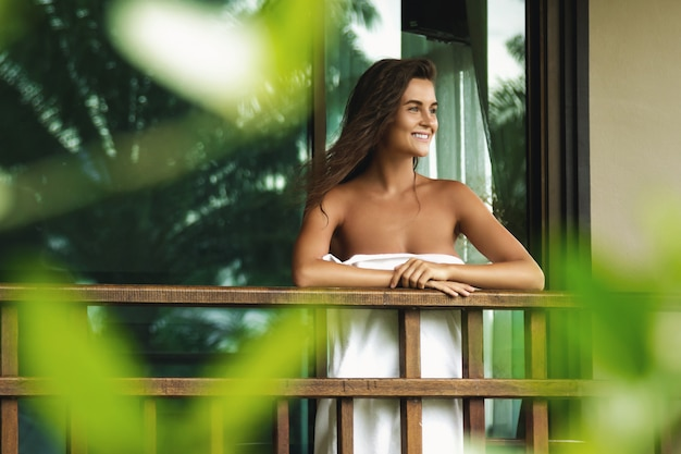Happy and beautiful woman on the balcony after shower