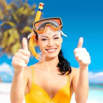 Happy beautiful woman on beach with thumbs up sign.