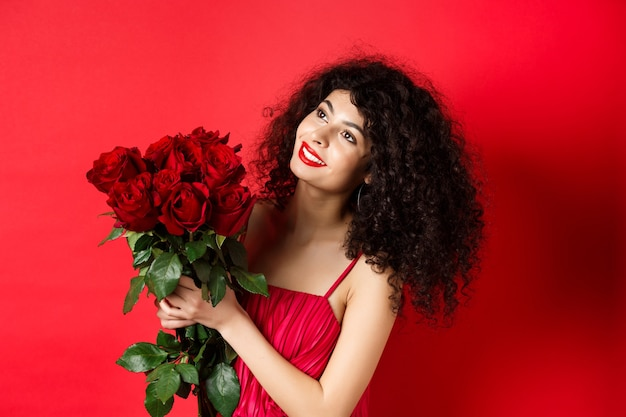Happy beautiful woman in dress, holding flowers and smiling romantic, looking aside at logo, standing against red background.