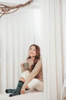 Счастливая красивая женщина пьет горячий кофе, сидя на подоконнике в доме, украшенном рождеством. концепция праздника