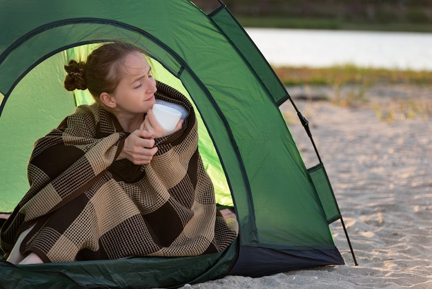 Happy beautiful woman enjoys sunny morning in camp. concept of travelling, hiking, camping.