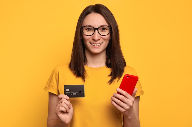 Happy beautiful woman in eyeglasses and yellow t-shirt using smartphone and credit card for online shopping in online store