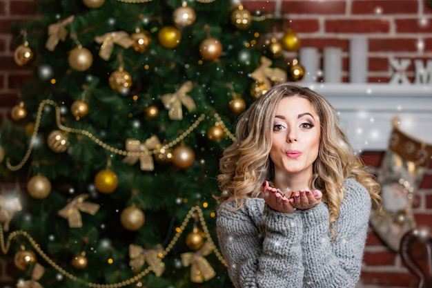 Happy beautiful woman in gray dress sends an air kiss on the background of a christmas tree with balls