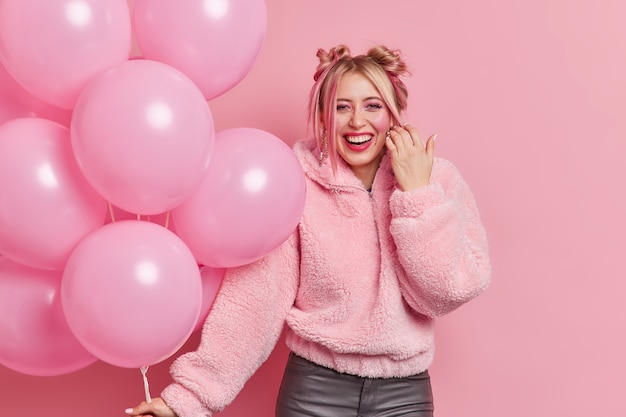 Happy beautiful woman has two buns dressed in fur coat smiles gladfully wears makeup holds bunch of inflated balloons enjoys partying and celebration