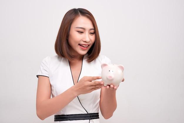 Счастливая красивая женщина держит в руках смешную копилку на белом