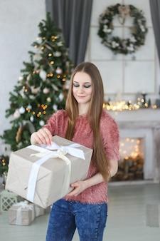 Счастливая красивая женщина, держащая большой рождественский подарок у дерева и камина дома