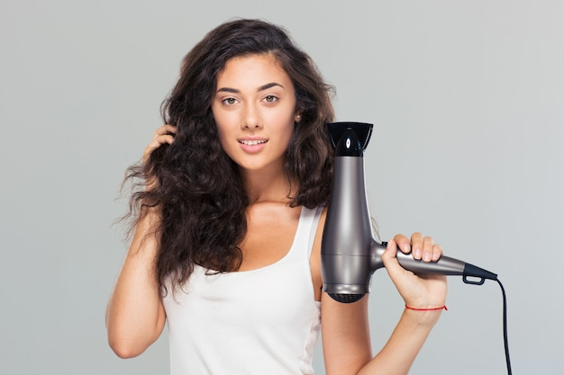Happy beautiful woman holding hairdryer