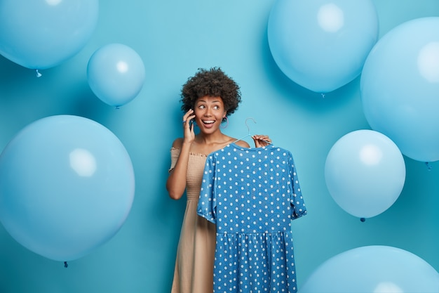 Happy beautiful woman holds blue polka dot dress on hanger, calls someone and uses her phone, prepares for special event, chooses outfit, poses around balloons. clothing, wardrobe, fashion concept