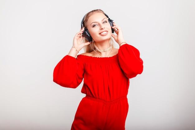 Счастливая красивая женщина в модном красном платье в наушниках позирует на сером. девушка слушает свою любимую музыку