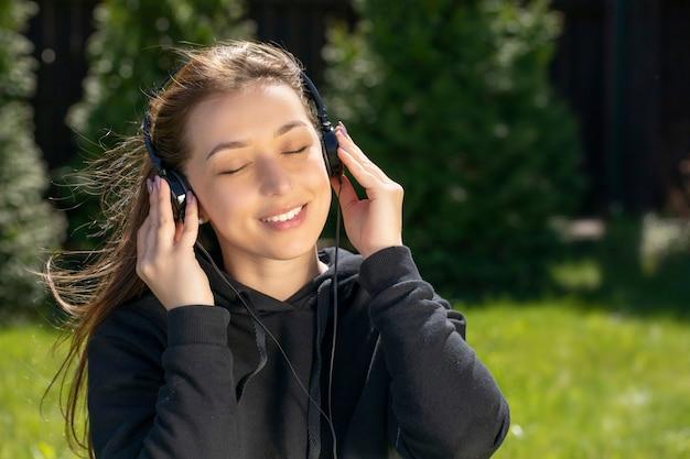 リラックスした音楽を聴いて、屋外で冷やしてヘッドフォンで幸せな美しい女性