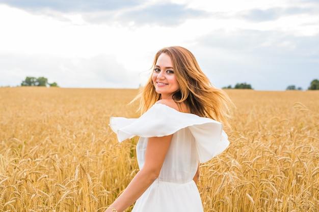 牧草地で幸せな美しい女性。自由の概念の背景。