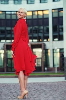 Счастливая красивая женщина в красном летнем платье гуляет и работает, радостная и веселая улыбка. летний день.