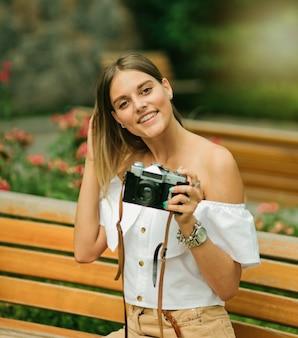 벤치에 앉아있는 동안 레트로 카메라를 들고 여름 옷에 행복 한 아름 다운 여자