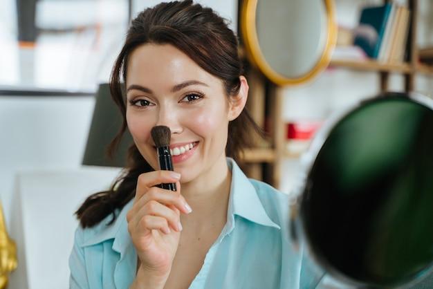 笑顔でカメラを見ている鏡の近くでポーズをとって家の中で幸せな美しい女性
