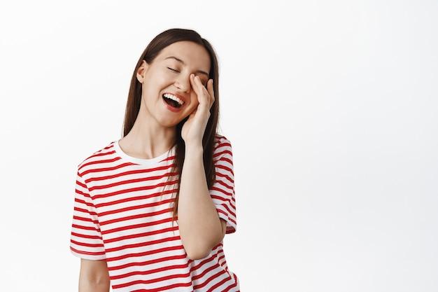 笑って、目を閉じて優しい表情で顔に触れ、のんびりと笑って、白い壁にtシャツで立って幸せな美しい女性