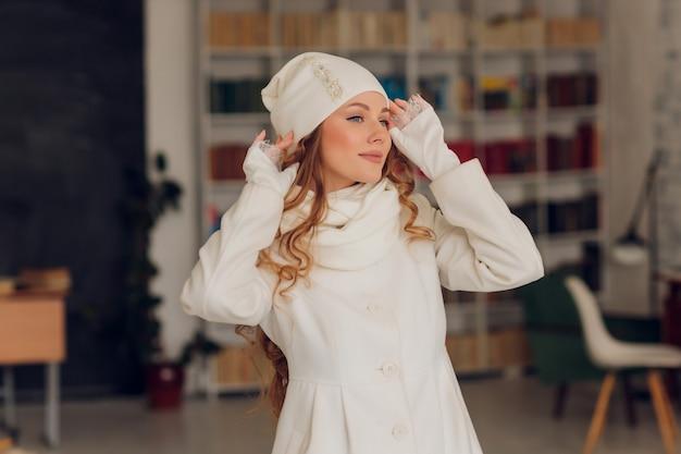 Счастливая красивая женщина смотрит в сторону в волнении. девушка в вязаной теплой шапке и варежках.