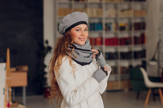 興奮して横向きに見える幸せな美しい女性。ニットの暖かい帽子とミトンを身に着けている女の子。
