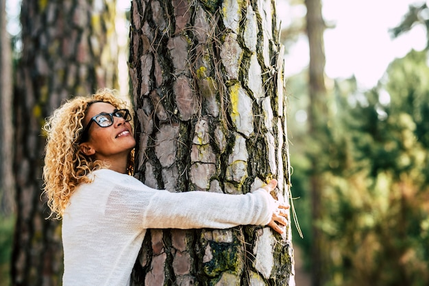 Happy beautiful woman love nature hugging a pine tree