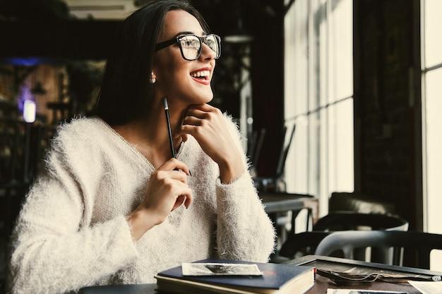 幸せな美しい女性がカフェに座っていくつかのメモを作る