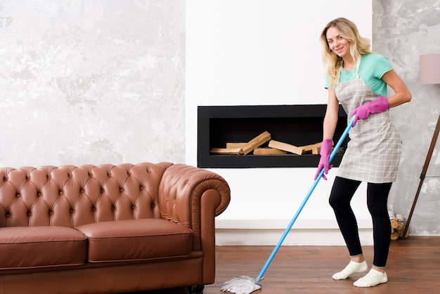 Happy beautiful woman mopping floor near couch at home