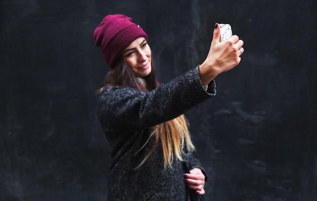 Счастливая красивая женщина теперь делает селфи на мобильном телефоне на черной стене