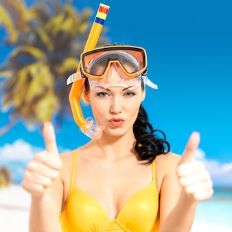 Счастливая красивая женщина на пляже с большими пальцами руки вверх знаком.