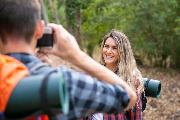 Счастливая красивая женщина позирует для фото и стоя на дороге в лесу. затуманенное парень фотографируя кавказских улыбается женщина-путешественница. походный туризм, приключения и концепция летних каникул