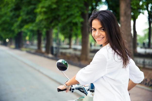 Счастливая красивая женщина, едущая на скутере