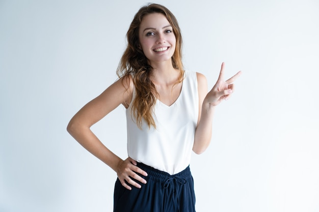 Happy beautiful woman showing victory sign and looking at camera
