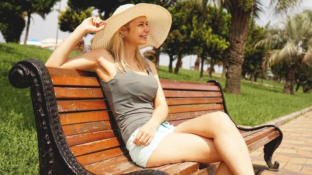 Счастливая красивая женщина сидит и смотрит на пляж