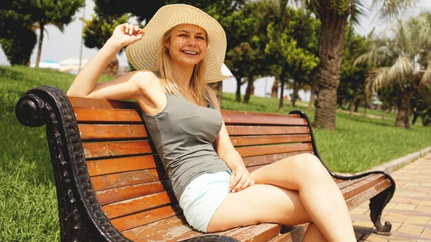 Happy beautiful woman sitting and looking the beach