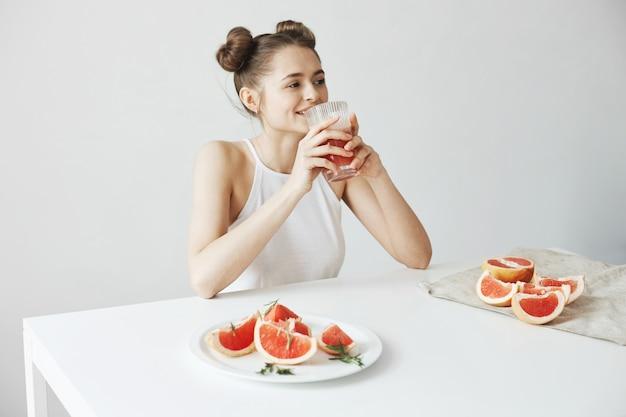 Seduta sorridente della bella donna felice alla tavola che beve il frullato fresco del pompelmo della disintossicazione sana sopra la parete bianca.