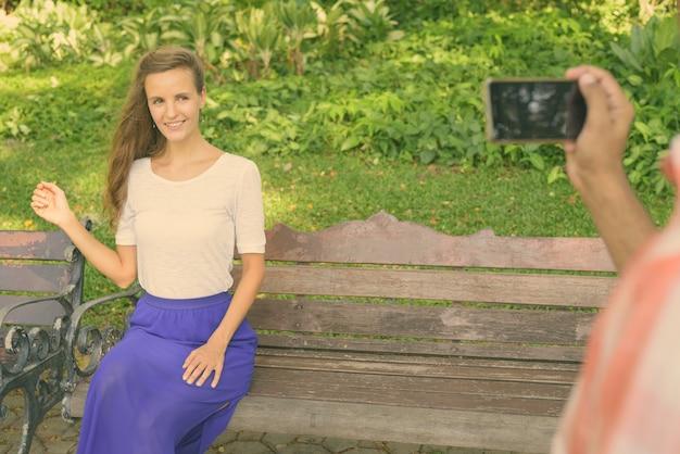 平和な緑豊かな公園で携帯電話で写真を撮るインド人と木製のベンチに座って笑っている幸せな美しい女性