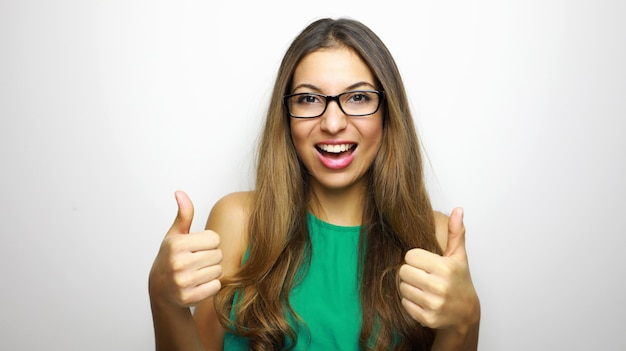 Happy beautiful woman in stylish black glasses and green dress showing thumbs up