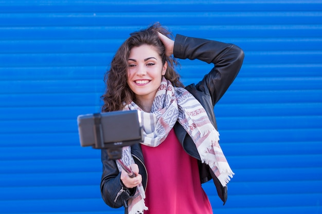 Happy beautiful woman taking a selfie with smart phone over blue background.