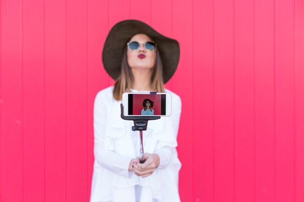 Happy beautiful woman taking a selfie with smartphone over red. wearing hat and sunglasses and using selfie stick