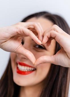 Пальцы счастливой красивой женщины касаясь в форме сердца и смотря камеру. веселая оптимистичная дама, чувствуя любовь. позаботьтесь о концепции здоровья