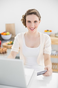 Happy beautiful woman using her notebook for home shopping sitting in kitchen