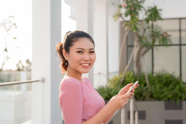 야외에서 스마트 폰을 사용하는 행복한 아름다운 여성