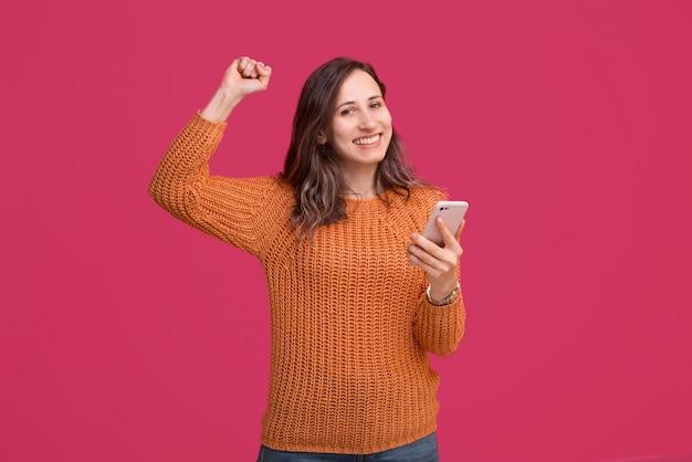 Счастливая красивая женщина используя smartphone и празднует победу