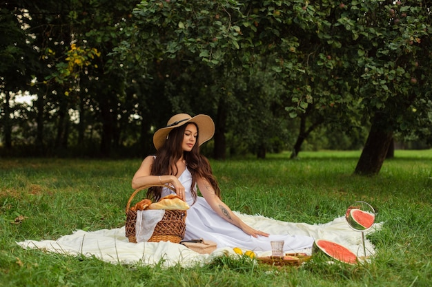 夏の公園で立ってパンのバスケットを保持しながらつばの帽子と白いドレスを着て幸せな美しい女性