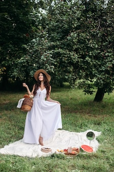 Happy beautiful woman wearing brimmed hat and white dress while standing and holding basket of bread in at summer park