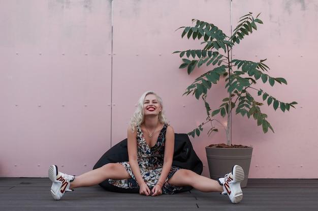 ピンクの壁の近くに座っている流行のファッションドレスで笑顔で幸せな美しい女性