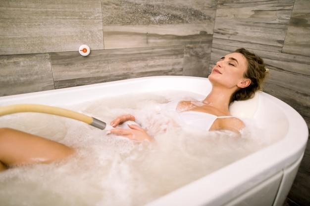 ウェルネスセンターのジャグジーバスタブでリラックスした目を閉じて幸せな美しい女笑顔します。ジャグジー風呂のスパで休んで若い女性